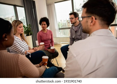 Diverse group of people sitting in circle in group therapy session.