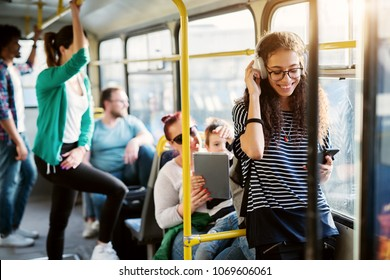 Diverse group of people is traveling by bus with the young adorable woman in the first plan of the picture who is smiling and listening to her music.