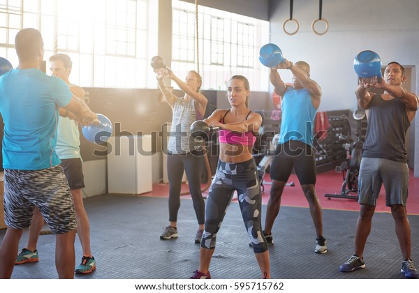 Diverse group of people working out training with kettlebells in industrial gym