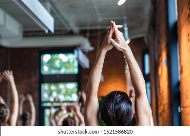 Diverse group of people in yoga class. A young woman is viewed close up and from behind as she stretched her arms towards the ceiling. Spiritual exercises during 108 sun salutes.