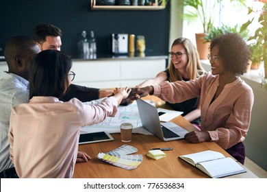 Diverse group of positive young businesspeople sitting around a boardroom table in an office with their hands together working as a team