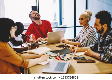 Diverse group of positive young people dressed in smart casual wear together with cheerful leader laughing and discussing ideas for developing startup project having brainstorming meeting in office