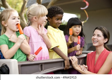 Diverse group of preschool 5 year old children playing in daycare with teacher