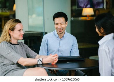A diverse group of professionals (lawyers, consultants or accountants) sit around a table and have a discussion to engage in business planning. A Chinese man, Caucasian woman and Indian woman talk.