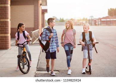 Diverse group of school kids talking and walking home from school together. Full length candid photo of both boys and girls leaving the school building on their bikes and scooters