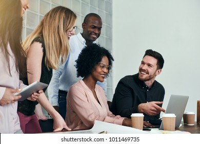 Diverse group of smiling business colleagues talking and working together on a laptop at a desk in a modern office