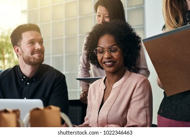 Diverse group of smiling business colleagues working together at a desk in a modern office