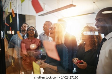 Diverse group of smiling businesspeople brainstorming together with sticky notes on a glass wall while working in a modern office