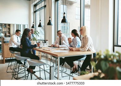 Diverse group of smiling businesspeople discussing paperwork together during a meeting around a table in a modern office