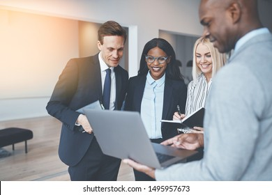 Diverse group of smiling businesspeople discussing work over a laptop while standing together in a bright modern office