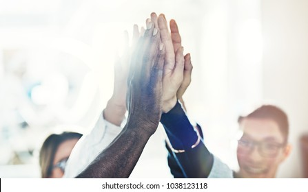 Diverse group of smiling businesspeople standing in a huddle in a bright modern office high fiving together