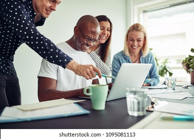 Diverse group of smiling businesspeople working online together with a laptop while sitting around a table in an office