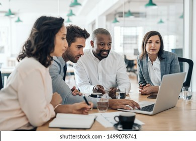 Diverse group of smiling businesspeople working together over a laptop during a meeting in the boardroom of a modern office
