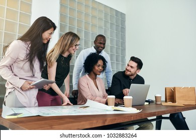Diverse group of smiling designers using a laptop and discussing blueprints while working together around a table in a modern office