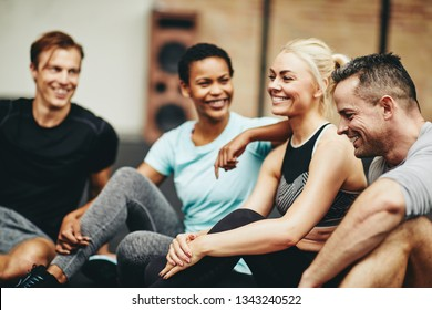 Diverse group of smiling friends in sportswear sitting together at the gym after a workout class