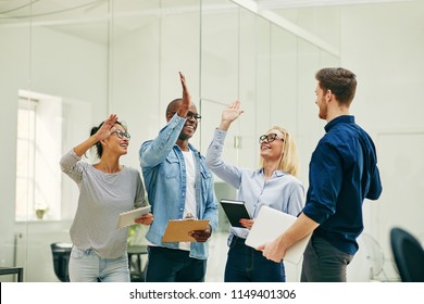 Diverse group of smiling young businesspeople celebrating success with high fives while working together in a modern office