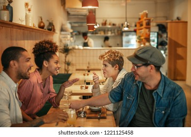Diverse group of smiling young friends talking together over dinner and drinks at a table in a trendy bistro