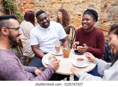Diverse group of smiling young friends sitting at a table in the courtyard of a trendy cafe chatting together over coffee