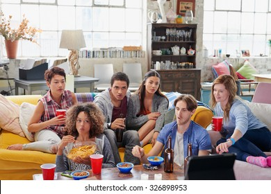 Diverse group of  student friends watching sports game on TV eager for winning goal sitting together drinking beer eating snacks at home