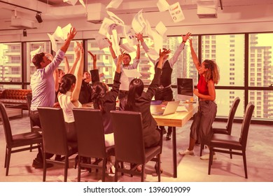Diverse group of successful business people meeting together throwing paper in the air with extremly happy feeling at modern office. Success team concept after sign contract in selective focus.
