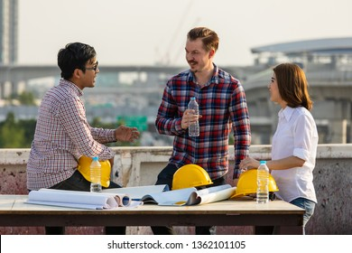 Diverse group of three engineer, caucacian and Asian, in construction site, take a break drinking water and talking together, brainstorm during working on rooftop of building
