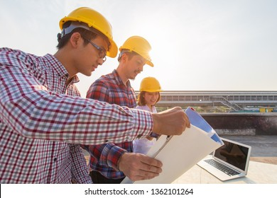 Diverse group of three engineer, caucacian and Asian, in construction site looking at blueprint plan and brainstorm during working on rooftop of building with beautiful sinlight in background