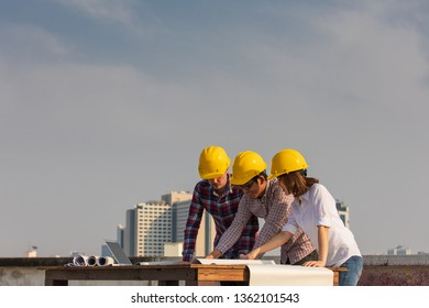 Diverse group of three engineer, caucacian and Asian, in construction site looking at blueprint plan and brainstorm during working on rooftop of building with copyspace on top.