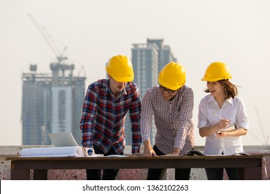 Diverse group of three engineer, caucacian and Asian, in construction site looking at blueprint plan and brainstorm during working on rooftop of building in beautiful sunlight.