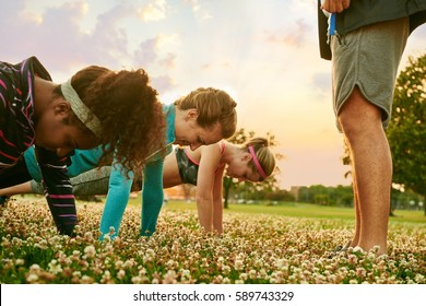 Diverse group of women during a fitness training doing push-ups at sunset in nature park