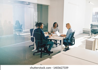 Diverse group of work colleagues laughing together during a meeting around a table inside of an office