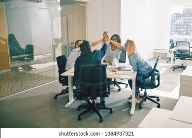 Diverse group of work colleagues smiling and high fiving together during a meeting around a table in a bright modern office