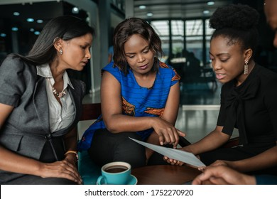 Diverse group of young African businesswomen going over paperwork together during a meeting in a modern office