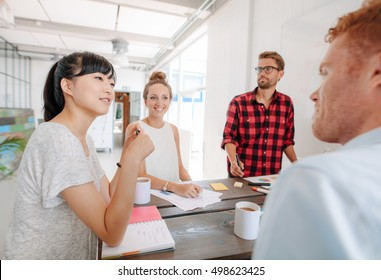 Diverse group of young business people at presentation in the office. Coworkers sitting around a table in modern office.