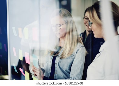 Diverse group of young businesspeople brainstorming with sticky notes on a glass wall while working together in a modern office
