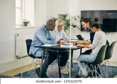 Diverse group of young businesspeople having a meeting together around a table inside of a glass walled boardroom