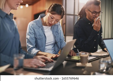 Diverse group of young businesspeople having a meeting together around a table in a modern office