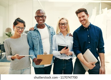 Diverse group of young businesspeople smiling while standing in a bright modern office working together