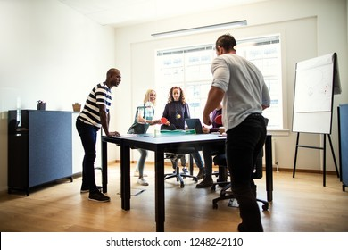 Diverse group of young designers laughing and playing table tennis on a boardroom table during a break from an office meeting