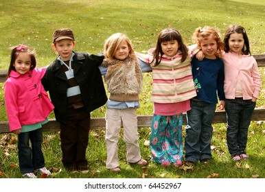 diverse group of young kids standing outside in fall