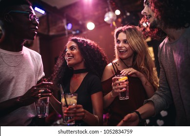 Diverse group of young people with drinks in a club. Happy men and women enjoying nightout at bar.