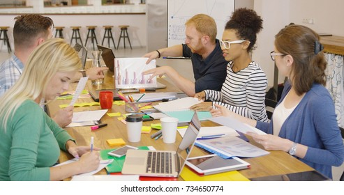 Diverse group of young people gathering at table in modern office and working with documents and gadgets creating new plan.