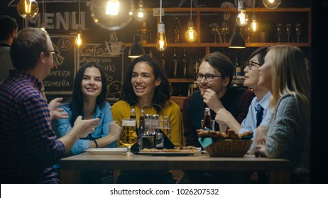 Diverse Group of Young People Have Fun in Bar, Have Conversation, Telling Stories and Jokes. They Drink Various Drinks. They're in the Stylish Hipster Restaurant.