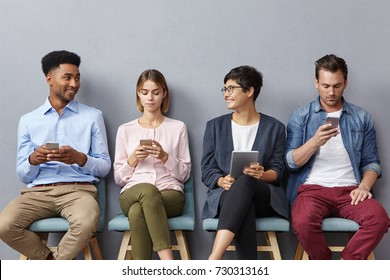 Diverse group of young people have lively conversation as sit in queue, use modern gadgets for different goals: communication, entertainement, searching information, surfing social networks.