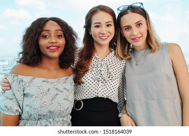 Diverse group of young pretty elegant businesswomen hugging and smiling at camera