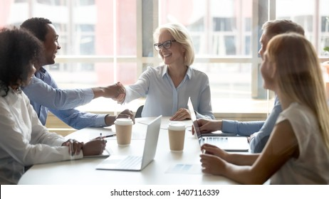 Diverse happy business partners handshaking signing contract after successful group negotiations make commercial deal commit agreement for services shake hands with client at corporate group meeting