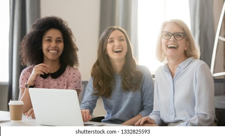 Diverse happy young and old businesswomen laughing looking away engaged in shared corporate meeting, joyful multi-ethnic women different age generation employees sit with laptop having fun at work