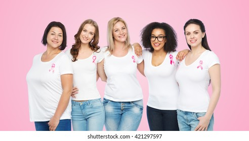 diverse, healthcare and people concept - group of happy different size women in white t-shirts with pink breast cancer awareness ribbon over pink background