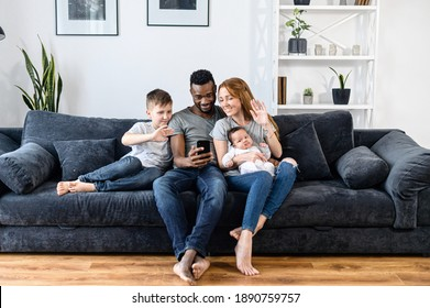 A diverse loving family of four using smartphone for video connection with family, friends, grandparents. A multiracial parents and their two childs on the sofa waving hello into webcam
