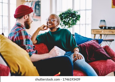 Diverse male and female hipsters having positive conversation enjoying together resting during weekend at home interior, cheerful couple in love talking about relationships at own designed apartment