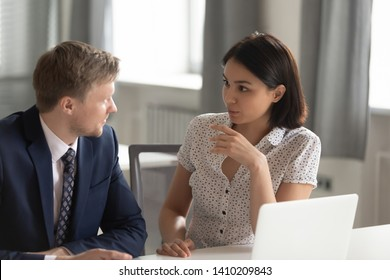 Diverse manager and client colleagues having business conversation at workplace, male and female executives talk at work share ideas discuss new project with laptop, teamwork advice at office meeting